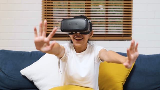 アジアの女性は vr ヘッドセットメガネを着用し、自宅でソファの上に座って virtural 現実を再生します。デジタル技術ライフスタイル - 仮想空間点の映像素材/bロール