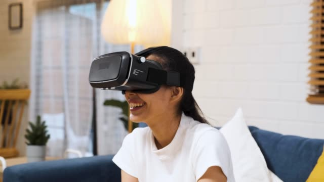 asian woman wear vr headset glasses and play virtural reality  sitting on sofa at home.digital tehcnology lifestyle.. - wearable computer stock videos & royalty-free footage