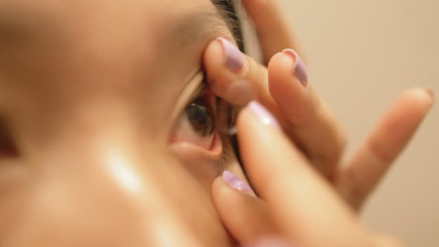 asian woman wearing contact lens in a bathroom - inserting stock videos & royalty-free footage