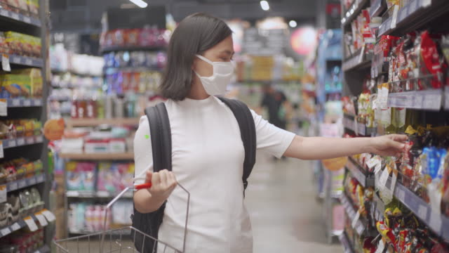 asian woman wearing face mask shopping in supermarket - freshness stock videos & royalty-free footage