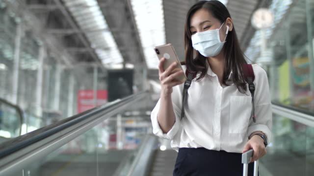 asiatische frau trägt gesichtsmaske mit handy am flughafen - passagierflugzeug stock-videos und b-roll-filmmaterial