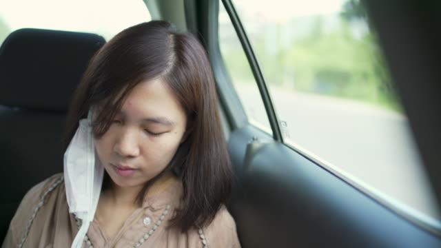 車に座ってスマートフォンのタッチスクリーンを使用してフェイスマスクを身に着けている4k cuアジアの女性。 - 柔軟性点の映像素材/bロール