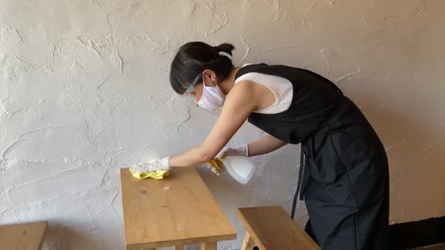 顔の盾と保護マスクのクリーニングテーブルを身に着けているアジアの女性 - 店点の映像素材/bロール