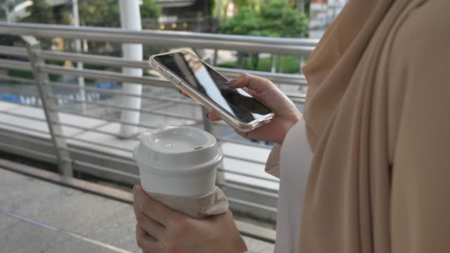 画面上のスマートフォン上の指を指し示す携帯電話を使用してヒジャーブを身に着けているアジアの女性 - 朝鮮半島点の映像素材/bロール