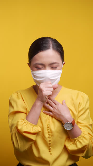 asian woman wearing hygiene mask was sick with sore throat and standing isolated over yellow background. 4k video. health care concepts. - thyroid gland stock videos & royalty-free footage