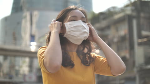asian woman wearing in face mask on street in the city outdoor - ecosystem stock videos & royalty-free footage