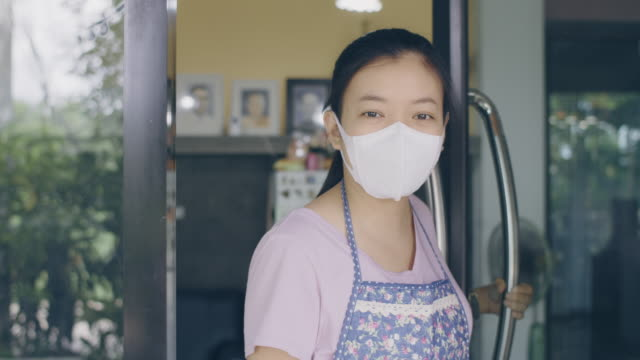 asian woman wearing mask standing with open sign board on glass door in coffee shop and restaurant after coronavirus lockdown quarantine.business crisis concept.4k slow motion. - only teenage girls stock videos & royalty-free footage