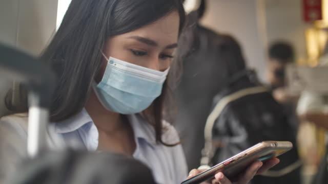 asiatische frau trägt maske, um corona-virus zu schützen - bahnreisender stock-videos und b-roll-filmmaterial