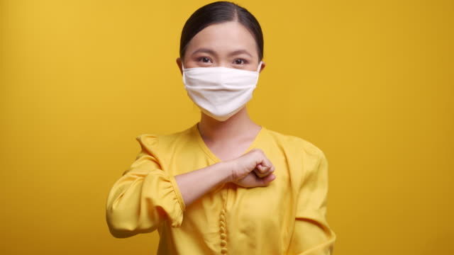 asian woman wearing protective face mask put her fist on a left chest isolated on yellow background. - respect stock videos & royalty-free footage