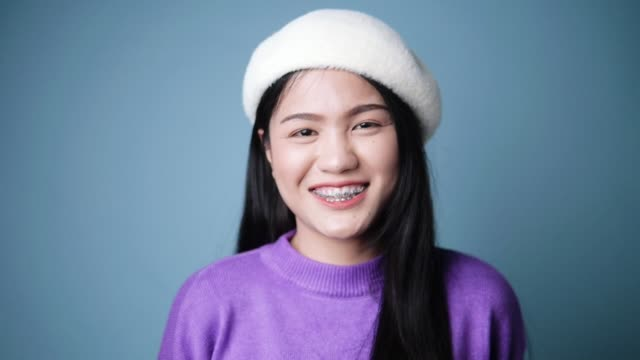 asian woman wearing purple sweater smiling on blue background, lifestyle concept. - comfortable stock videos & royalty-free footage