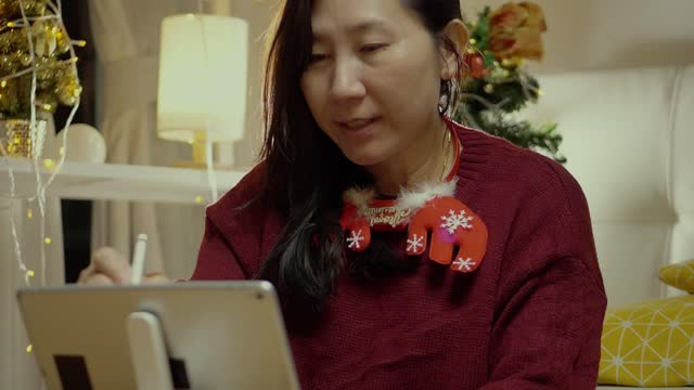 asian woman wearing sweater using pencil and digital tablet at home with christmas decorations background, work from home concept. - pencil isolated stock videos & royalty-free footage