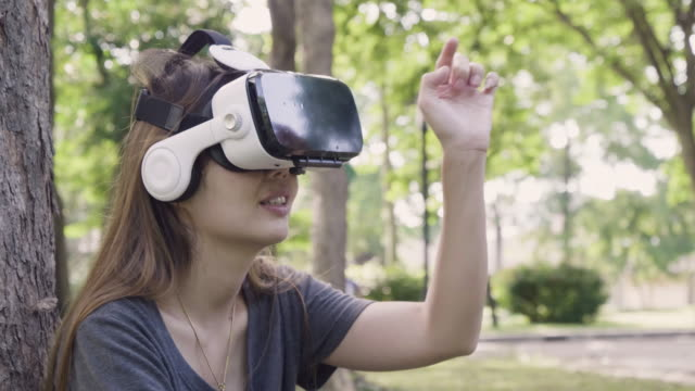 Asian Woman Wearing Virtual Reality Headset In The Park