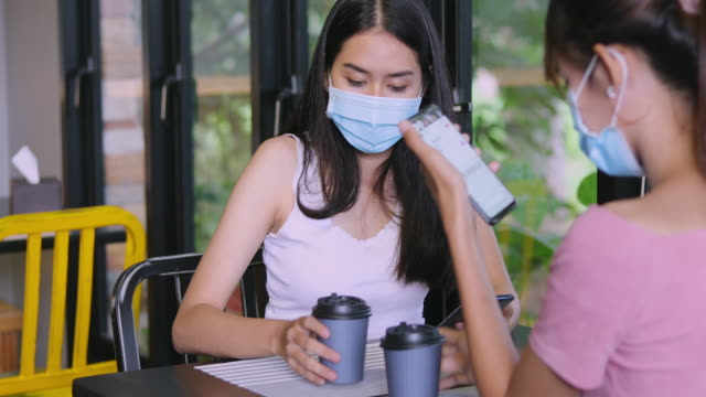 vídeos de stock e filmes b-roll de asian woman with a friend playing on the phone and drinking hot coffee in a coffee shop being served drinks by the waitress and both of you wear masks - trabalhadora de colarinho branco