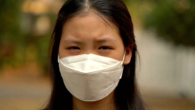 4k cu asian woman with air pollution mask looking at camera - pollution mask stock videos and b-roll footage