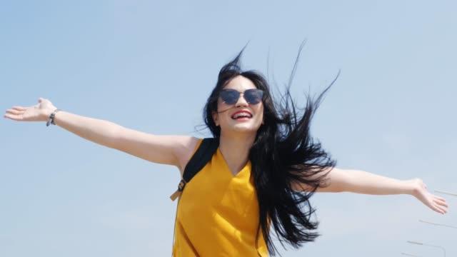 vidéos et rushes de femme asiatique avec des mains de soulèvement de sac à dos avec le ciel bleu. - seulement des femmes