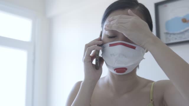 vidéos et rushes de femme asiatique avec la protection de masque de visage du coronavirus, appelant l'occupation de services d'urgence - accident et désastre