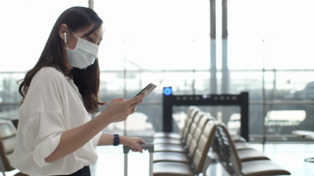 asian woman with face mask using mobile phone while walking to travel at airport, slow motion - briefcase stock videos & royalty-free footage