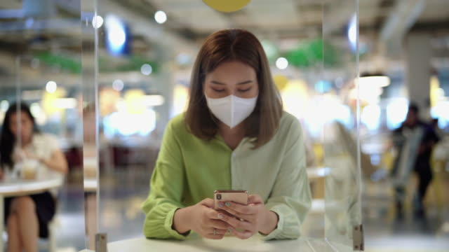 a asian woman with hygienic mask and using smartphone on cafe - food and drink establishment stock videos & royalty-free footage