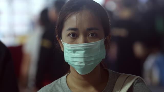 vídeos de stock, filmes e b-roll de mulher asiática com máscara higiênica - tossindo