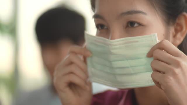 vidéos et rushes de femme asiatique avec le masque hygiénique - appliquer