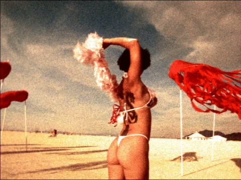 grainy rear view asian woman with large tattoo on back in bikini dancing with feather boa on windy beach - bikini stock-videos und b-roll-filmmaterial