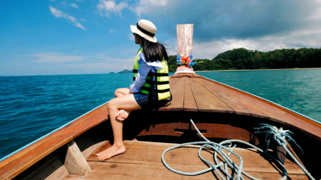 Asian Woman with life jacket in Thai Taxi Boat at Railay, Krabi, Thailand