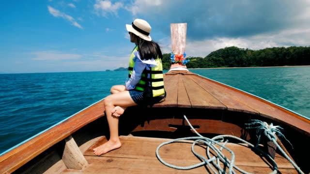 Asiatisk kvinna med flytväst i thailändska taxibåt på Railay, Krabi, Thailand
