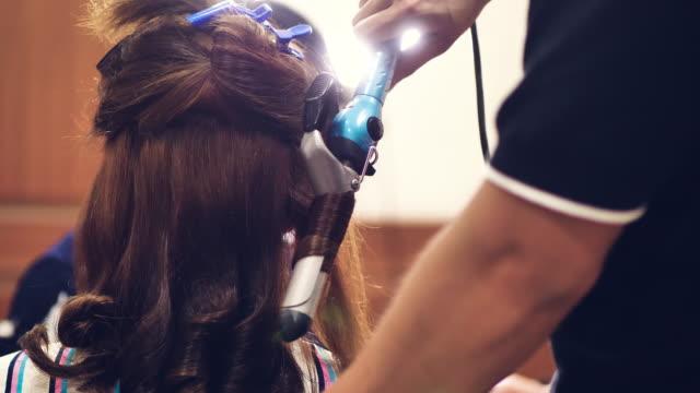 vídeos de stock, filmes e b-roll de mulher asiática com cabelo comprido e cabeleireiro com ferro fazendo do cabelo fazer. - cabelo encaracolado