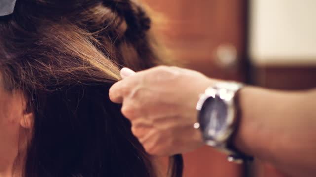 asiatisk kvinna med långt hår och frisör med hår järn gör hår gör. - spole bildbanksvideor och videomaterial från bakom kulisserna