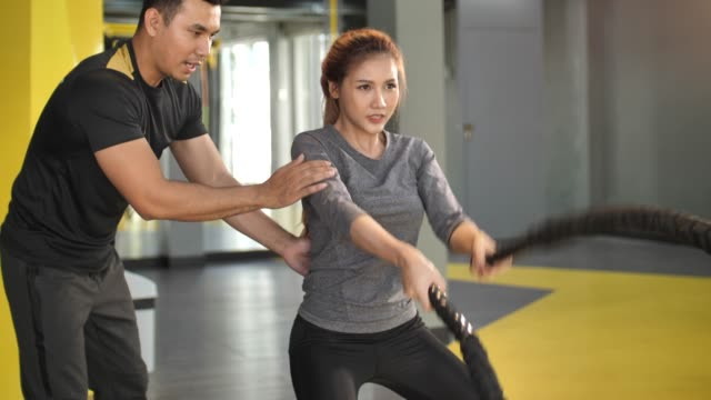 asian woman with personal trainer working out with battle ropes in gym - battle stock videos & royalty-free footage