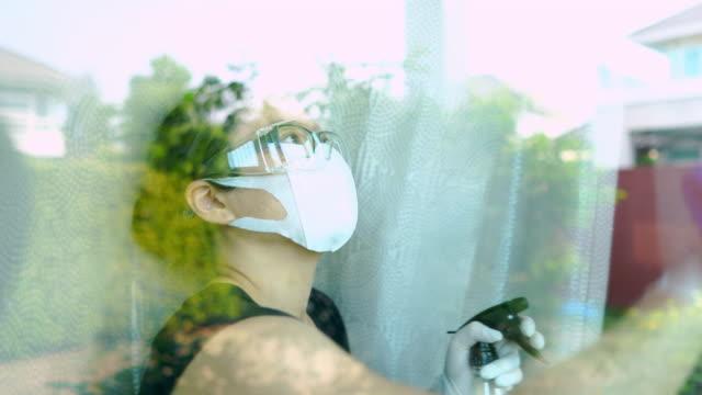 stockvideo's en b-roll-footage met aziatische vrouw met veiligheidsglazen en gezichtsmasker met handhandschoen die alcohol bespuit en het schoonmaken van het venster - huishoudelijke dienstverlening