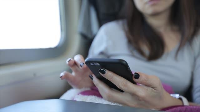 4k: asiatin mit smartphone während der fahrt mit dem zug - teenage girls stock-videos und b-roll-filmmaterial