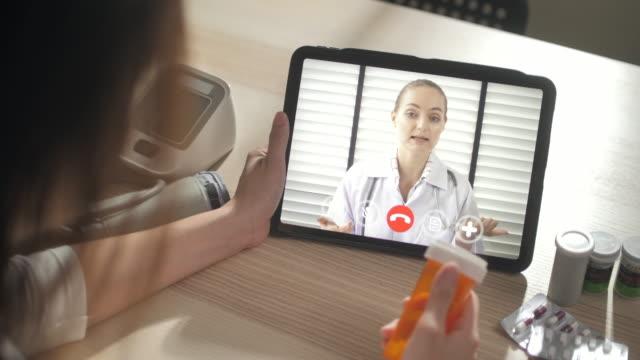 donna asiatica donna che parla con il medico in webcam online video chat su tablet digitale - dottoressa video stock e b–roll