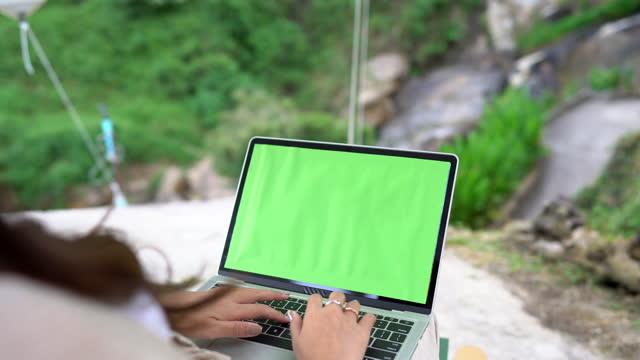vídeos y material grabado en eventos de stock de mujer asiática trabaja en portátil sentado en una silla en la naturaleza mientras acampa, clave cromática - área silvestre
