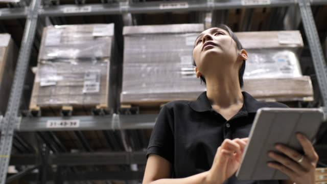 asian woman worker checking supplies using digital tablet in the warehouse - deposito video stock e b–roll