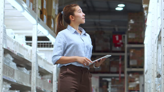 vídeos de stock e filmes b-roll de asian woman worker working using tablet checking boxes logistic import and export supplies packages in warehouse , logistics concept - classificados