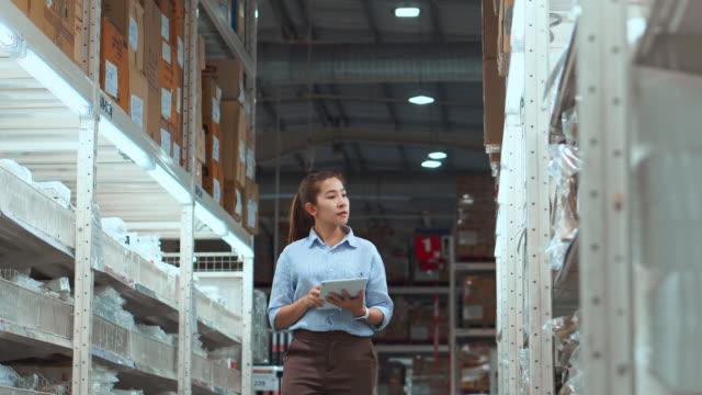 タブレットチェックボックスを使用して働くアジアの女性労働者倉庫、物流コンセプトのロジスティクス輸出入品パッケージ - コンピュータハードウェア点の映像素材/bロール