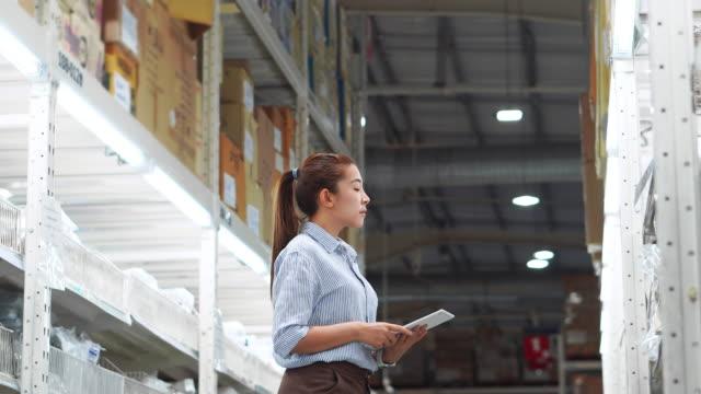 vidéos et rushes de travailleur asiatique de femme travaillant utilisant des boîtes de cochez des boîtes logistiques d'importation et d'exportation des paquets dans l'entrepôt, concept logistique - société de consommation