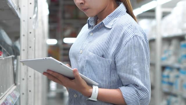 vídeos y material grabado en eventos de stock de mujer trabajadora asiática que trabaja usando cajas de verificación de tabletas importación logística y exportación de suministros paquetes en almacén , concepto logístico - cuarto almacén