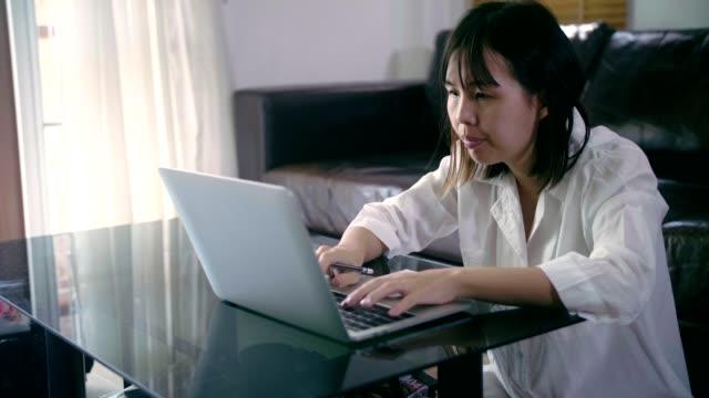 vidéos et rushes de asiatique femme travaillant à son bureau à domicile - engagement des clients