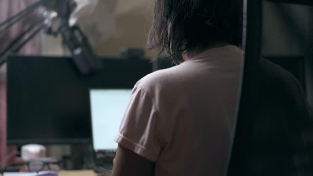 vidéos et rushes de femme asiatique travaillant à la maison utilisant l'ordinateur portatif - doigt humain