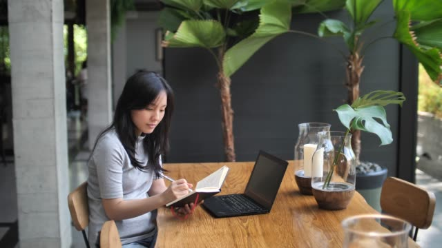 asian woman working in cafe and writing notes while drinking coffee, freelance work - coworking stock videos & royalty-free footage