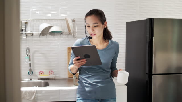 asian woman working on her digital tablet and video conference talking with colleague at home - home office stock videos & royalty-free footage