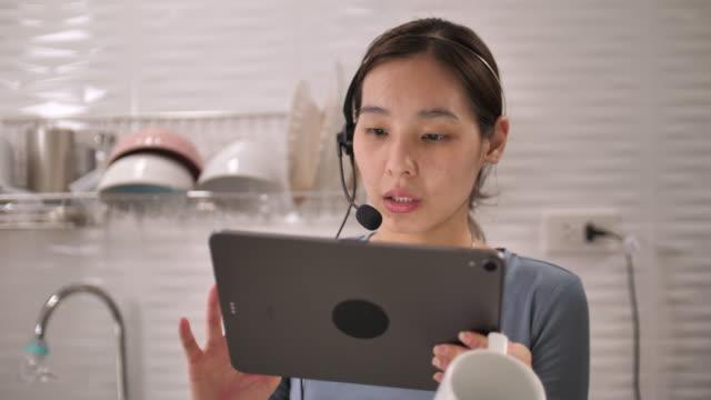 自宅で同僚と話している彼女のデジタルタブレットとビデオ会議に取り組んでいるアジアの女性 - ヘッドセット点の映像素材/bロール