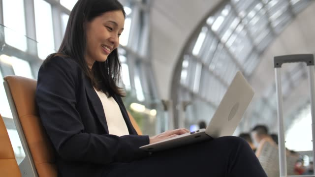 asian woman working on her laptop in the airport - tourist stock videos & royalty-free footage