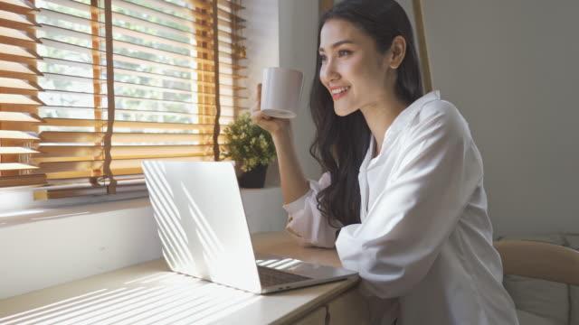 vídeos de stock, filmes e b-roll de mulher asiática trabalhando em laptop e bebendo café - manhã