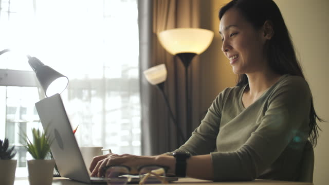 asian woman working on laptop at home - home office stock videos & royalty-free footage