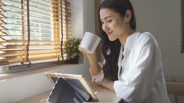 asian woman working on tablet and drinking coffee - popolazione dell'asia orientale video stock e b–roll