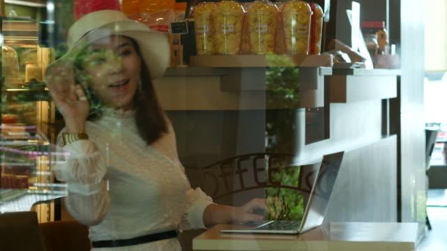 asiatische frau mit laptop im café, hallo zeichen online arbeiten - sportschützer stock-videos und b-roll-filmmaterial