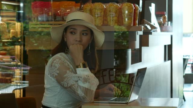 asiatische frau mit laptop im café online arbeiten - sportschützer stock-videos und b-roll-filmmaterial